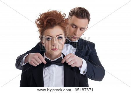 Gallant man straightens tie to his sexy girlfriend