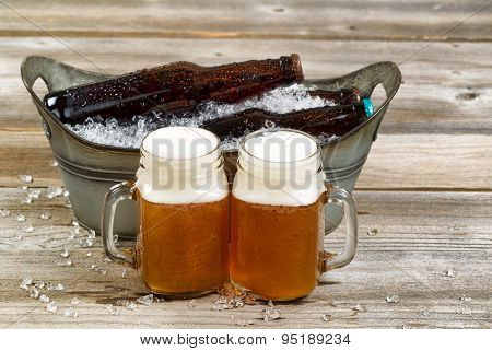 Two Pints Of Fresh Cold Beer In Front Of Bucket Filled With Ice On Rustic Wooden Boards