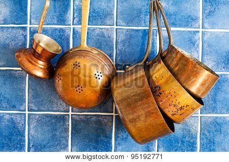 Aged Copper Utensils. Hang On Iron Hooks Against Blue Tile Wall.