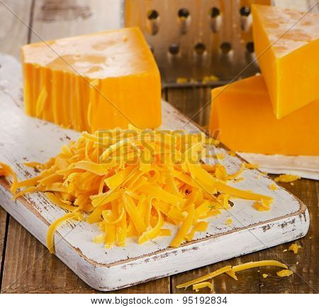 Grated Cheddar Cheese On  Wooden Cutting Board.