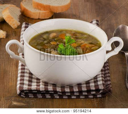 Bowl Of Soup With Lentils, Beans, Chicken And Vegetables On A Rustic Wooden Table.