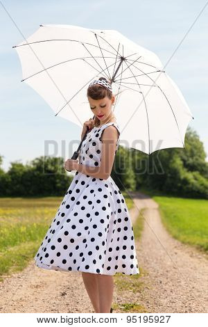 Fifties Look With Petticoat Dress, Hairband Und Sunshade In The Nature