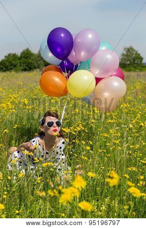 Pin Up Girl On A Flowery Meadow With Colorful Balloons