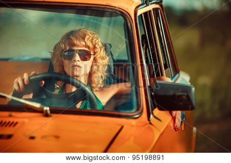 Woman Is Driving An Old Yellow Car. Rural Background.