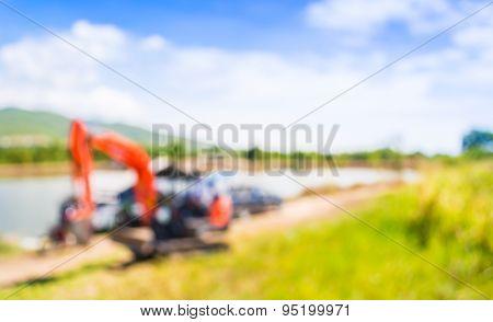 Blur Image Of Orange Excavator Doing Lake Construction.