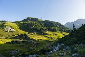 stock photo of italian alps  - High voltage power line crossing idyllic alpine environment hit by the first sunlight of the day - JPG