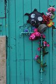picture of gas mask  - Gas mask and artificial flowers on the old wooden door - JPG