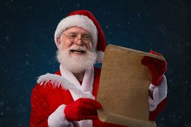 picture of letters to santa claus  - Happy Santa Claus reading a letter or a wish list - JPG