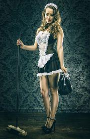 stock photo of maids  - Pretty Vintage sexy maid housemaid on dark - JPG