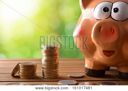 Closeup Piggy Bank With Coins On Table And Nature Background