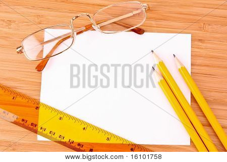 Pencils, paper, glasses and ruler on wooden table