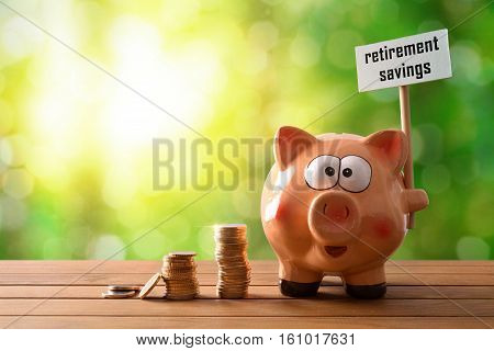 Piggy Bank With Billboard Retirement Savings On Table Nature Background