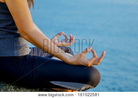 The Woman Meditating In A Yoga Pose On The Tropical Beach. Female Meditating Overlooking The Beautif