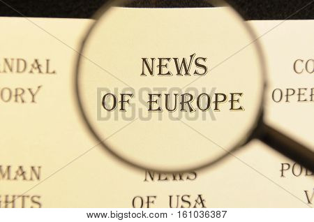 Text through the hand magnifying glass on the headline of the article - for the use of newspaper editor