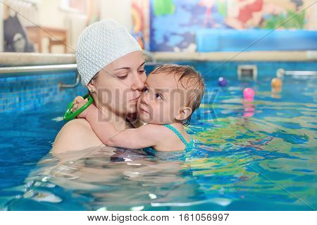 Adorable baby girl enjoying swimming in a pool with her mother, early development class for infants teaching children to swim