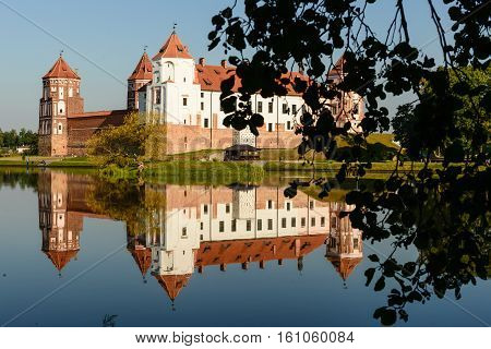 Mir, Belarus - August 28,2016:  Medieval castle in the Belarusian town of Mir with reflection in a pond framed by the of leaves of trees