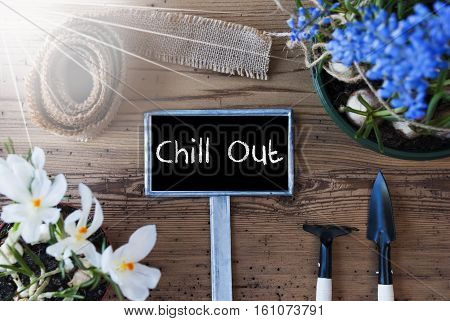 Sign With English Text Chill Out. Sunny Spring Flowers Like Grape Hyacinth And Crocus. Gardening Tools Like Rake And Shovel. Hemp Fabric Ribbon. Aged Wooden Background
