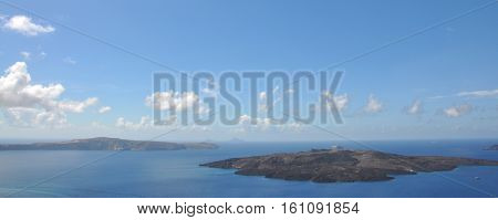 panorama of Nea Kameni, a small uninhabited Greek island of volcanic origin located in the Aegean Sea and Santorini caldera. light blue color