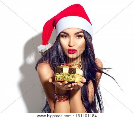 Beauty Christmas fashion model girl holding Xmas gift box. Beautiful lady, Long straight flying hair, red santa hat, holding gift box. Sexy brunette young woman portrait isolated on white background