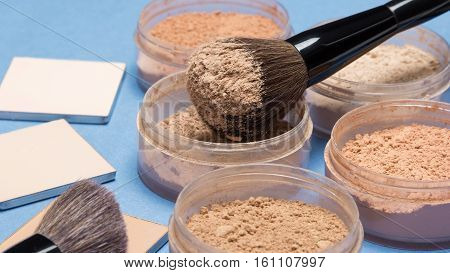 Loose and compact cosmetic powder different shades with makeup brushes on blue background. Side view, selective focus