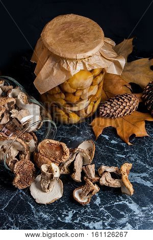 Two Glass Jars With Wild Mushrooms On Black Marble Background.