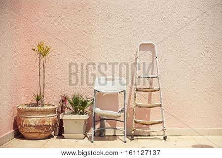 Mainstream fashion photo. Objects standing in a row stepladder chair pot on wall background