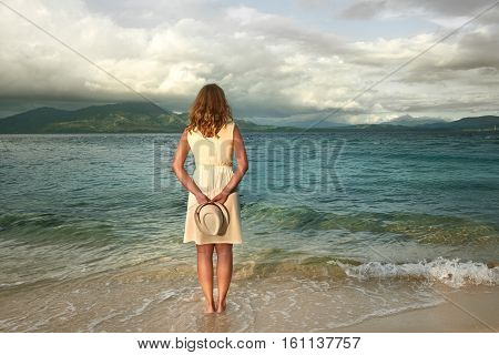 Portrait young girl wearing white dress on a beach before the rain on a background of the dramatic sea and islands. Beach sunset nature evening. concept love romance.