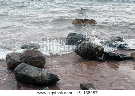 Waves breaking on large boulders on the shore of Lake Superior, Marquette County, Michigan, USA