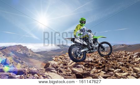 Brave professional dirt bike rider pose on the top of vulcan