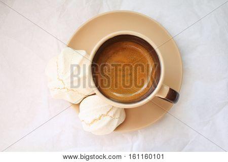 Espresso coffee and meringue cookies. Top view