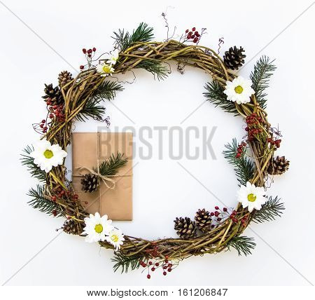Festive wreath of grape vines decorated with berries fir branches daisy flowers and cones. Present wrapped in eco paper. Christmas DIY wreath. New Year round wreath on white background. Flat lay top view