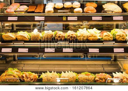 Bright shot of burgers donuts and sandwiches in a bakery or shop glass counter. Shiny showcase of baked fastfood with prices