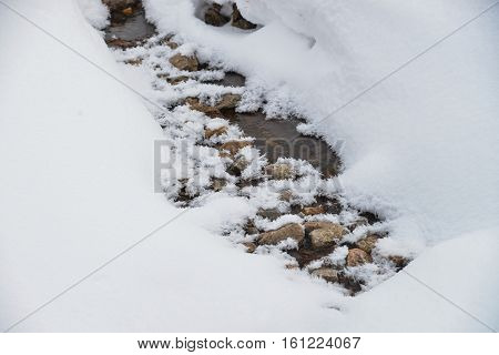 Mountain stream running covered by snow in winter with some stones in water.