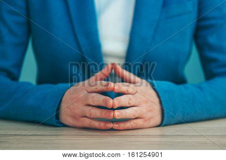 Businesswoman body language for confidence and self-esteem hands with steepled fingers on office desk