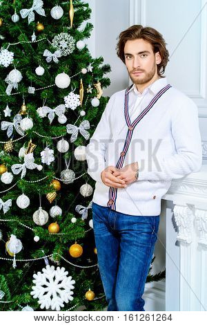 Christmas concept, male fashion. Handsome young man in elegant cardigan posing in luxurious apartments decorated for Christmas. Hairstyle.