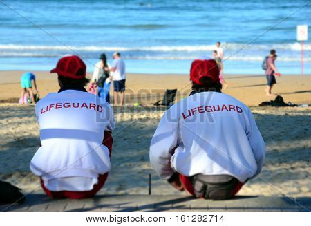 Two lifeguards sitting on the rock fence and watching the people on the beach. Focus on the jumper's title: LIFEGUARD. Sydney Manly beach lifeguard looking out for people.