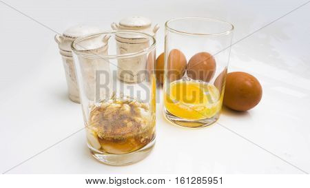 Parboiled egg semi raw macro photo behide are raw egg in clear glass jars salt and pepperLeaf shadow too soft on white background.