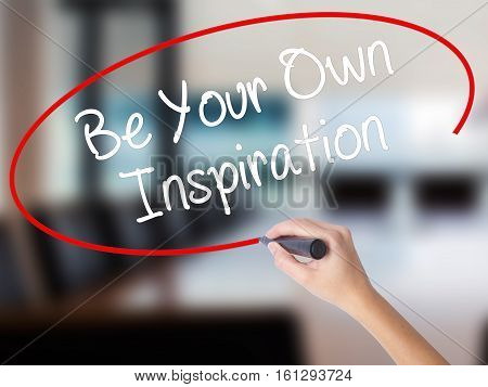 Woman Hand Writing Be Your Own Inspiration With A Marker Over Transparent Board.