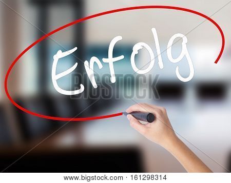 Woman Hand Writing Erfolg Success (in German) With A Marker Over Transparent Board