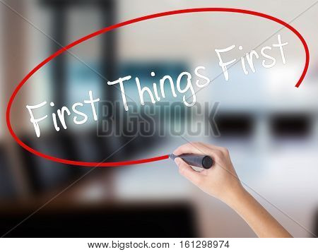 Woman Hand Writing First Things First With A Marker Over Transparent Board