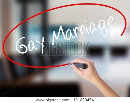 Woman Hand Writing Gay Marriage With A Marker Over Transparent Board.