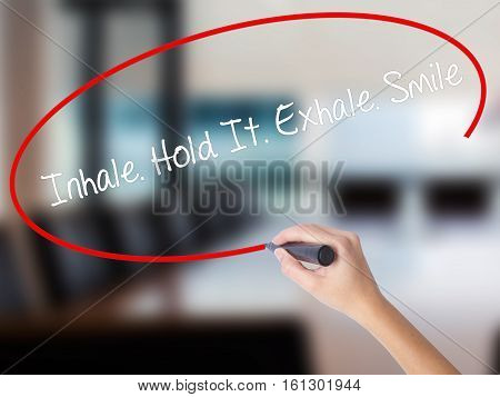 Woman Hand Writing Inhale Hold It Exhale Smile With A Marker Over Transparent Board