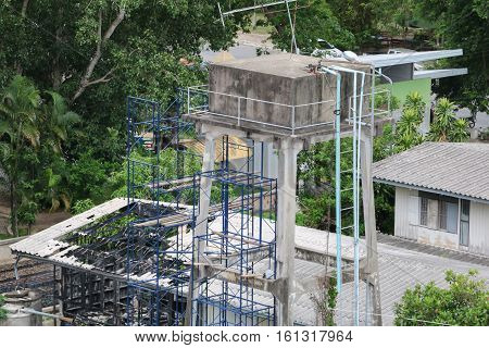 Water tank and scaffolding in repair for agriculture with blue sky background