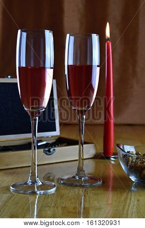 Set of wine in a wooden box. Two glasses with rose wine and a candle. Wine.