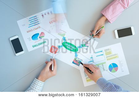 Top View of Hands of Business People Meeting on grey Table with professional Charts