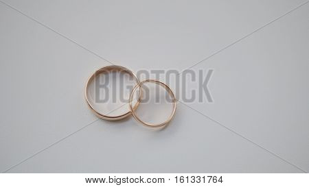 Golden wedding rings in center of white background, close up
