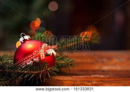 red Christmas decoration in front of burning fireplace and holiday lights - cozy home