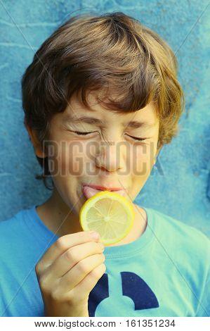 preteen handsome boy eating lemon with sore grimace close up outdoor portrait