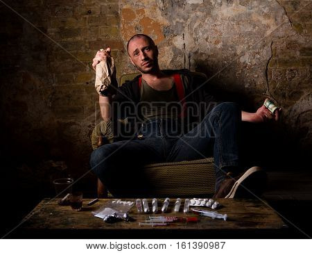 Image of drug mafia, cartels, dealers. Drug dealer drinking alcohol drinks and using different types of narcotics. Drugs selling concept.