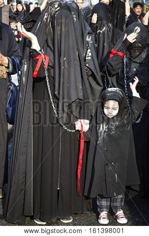 Istanbul Turkey - October 11 2016: Turkish Shia women takes part in an Ashura parade in Istanbul's district of Kucukcekmece. Turkish Shia Muslims mourning for Imam Hussain. Women and young girls muddy on top of them to accomodate the chronology of mournin